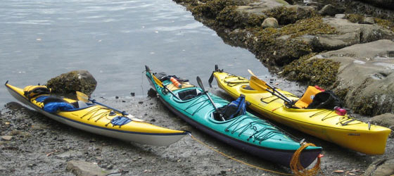 Three kayaks, paddles, and life vests waiting on rocky shore